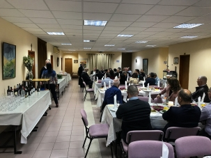 Meal on table on left, people gathered